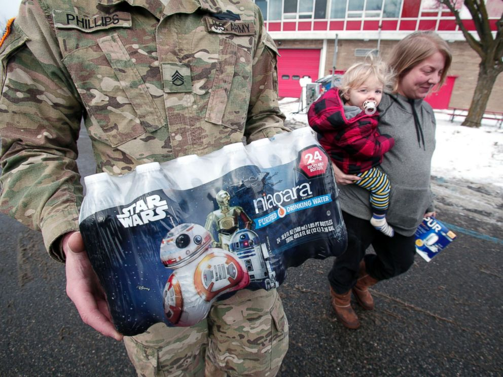 PHOTO: Michigan National Guard Staff Sergeant William Phillips of Birch Run, Michigan, helps Flint resident Amanda Roark and her son Dash take bottled water out to her vehicle after she received it at a Flint Fire Station Jan. 13, 2016 in Flint, Michigan.