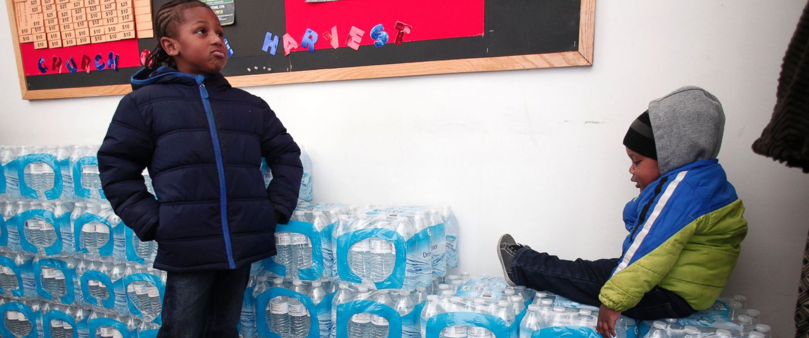 PHOTO: Justin Roberson (L), age 6, of Flint, Michigan and Mychal Adams, age 1, of Flint wait on a stack of bottled water at a rally where the Rev. Jesse Jackson was speaking about the water crisis on Jan. 17, 2016 in Flint, Michigan.