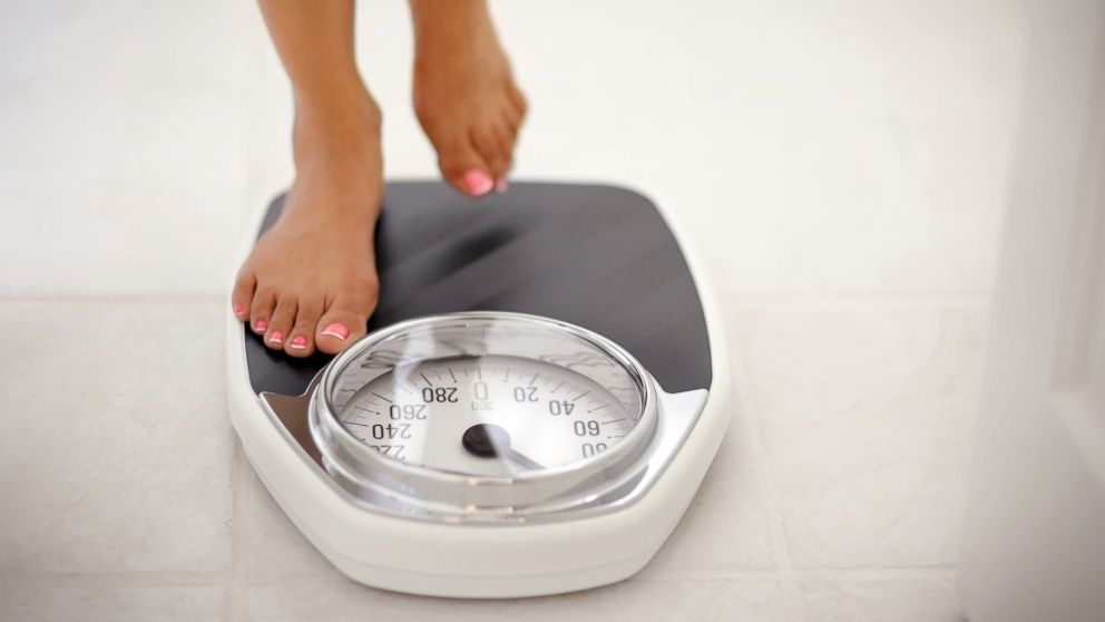 PHOTO: A woman stands on a bathroom scale in this undated stock photo.