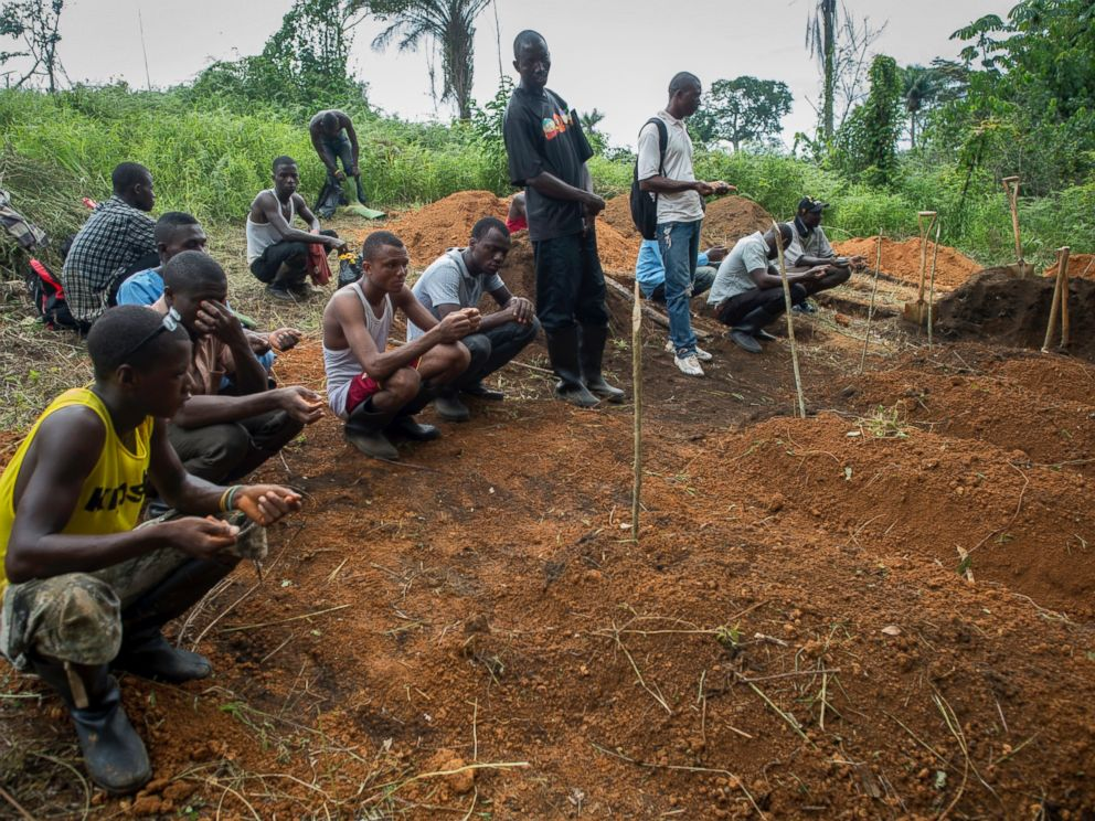 PHOTO: A World Health Organization (WHO) team is burying the deceased patients whose families did not come in the forest near the MSF Treatment Centre in Kailahun, Sierra Leone.