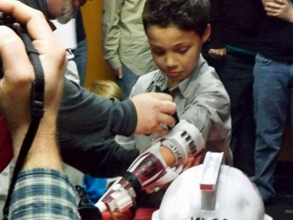 PHOTO: Liam Porter receives a Clone Trooper prosthetic arm from the charity group, E-Nable