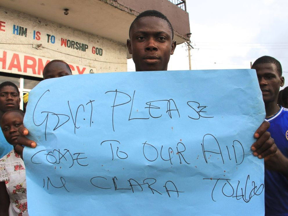 PHOTO: A young man holds a sign at a protest about the delayed removal of a suspected Ebola victim who had died in Clara Town, Liberia, on Thursday. On Saturday morning, community members learned that the dead mans neighbor had also died.