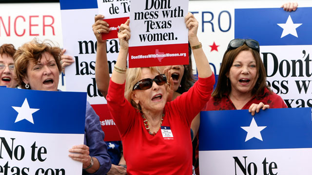 PHOTO: Mary Green, Peg Armstrong and Jan Perrault hold up signs during Womens Health Express, a bus event held in San Antonio, Texas, to protest the attempt to cut Planned Parenthood out of the states Womens Health Plan, March 6, 2012.