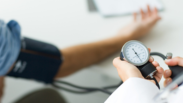PHOTO: Doctor checking patients blood pressure