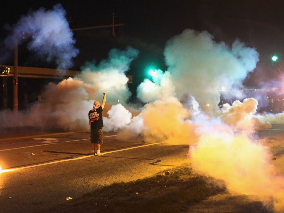 PHOTO: A demonstrator, protesting the shooting death of teenager Michael Brown, stands his ground as police fire tear gas on August 13, 2014 in Ferguson, Missouri.