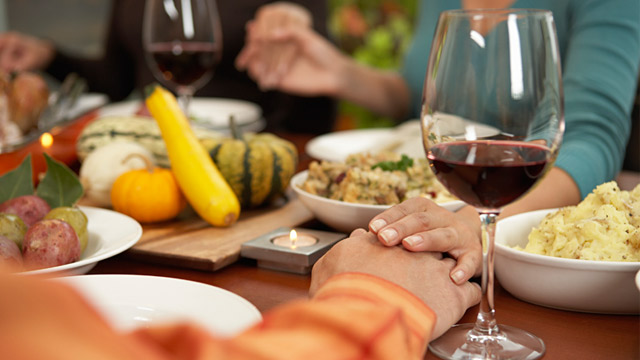 PHOTO: People holding hands at dining table