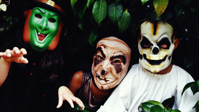 PHOTO: Three children wear halloween masks.