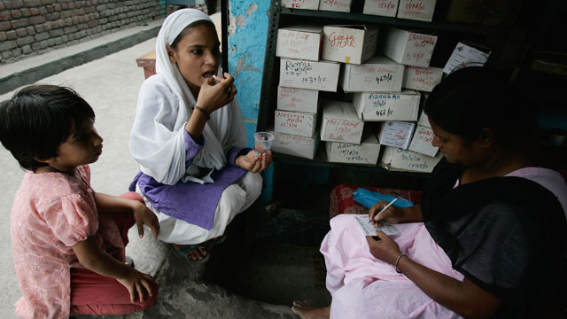 PHOTO: A counselor watches as a tuberculosis (TB) patient takes her medication at an operation ASHA ('hope' in Hindi) treatment center on June 2, 2011, in New Delhi, India.