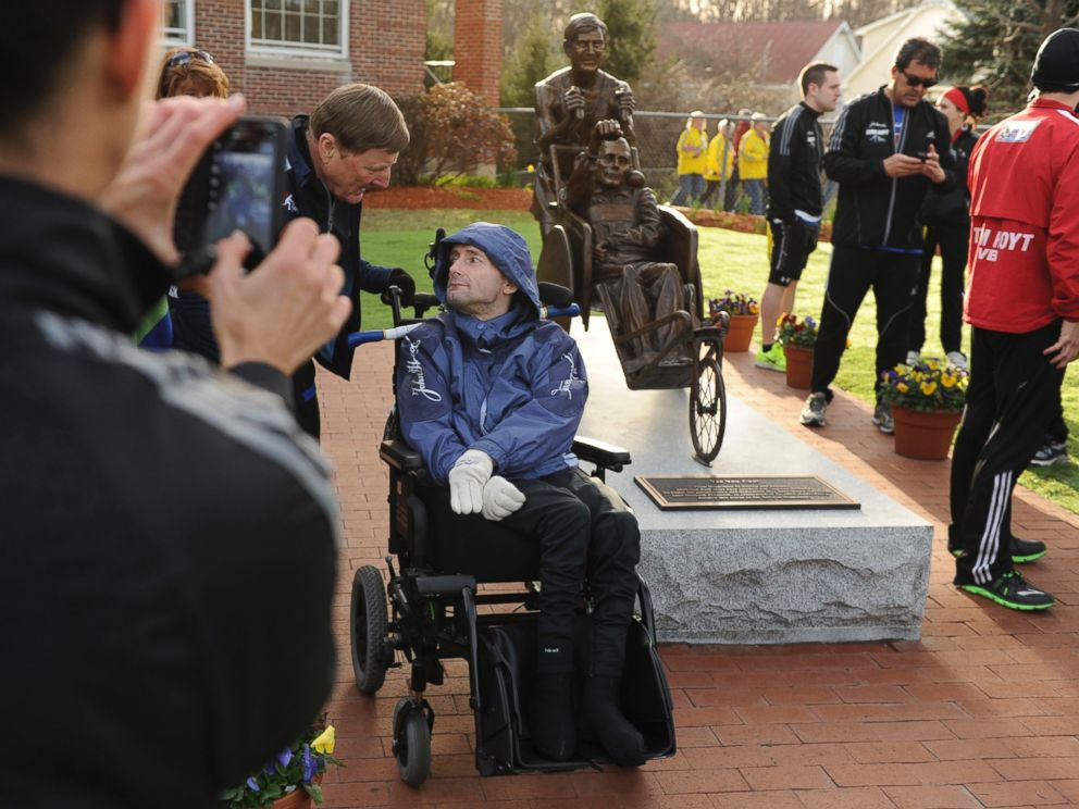 PHOTO: Dick Hoyt, left, and his son, Rick, pose for photos by their statue at the start of the Boston Marathon in Hopkinton, Mass., on April 15, 2013.