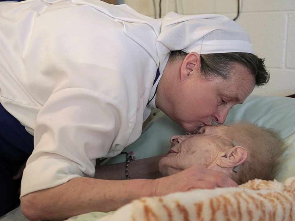 PHOTO: Sister Stephen kisses a dying patient.