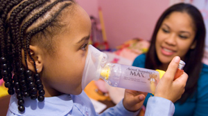 PHOTO A nurse works with a child during a home visit as part of the Community Asthma Initiative.