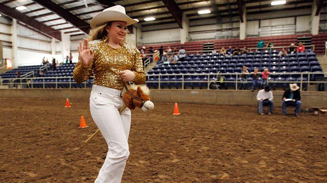 PHOTO:Jaclynn Brooks smiles and waves as she rides her stick horse.