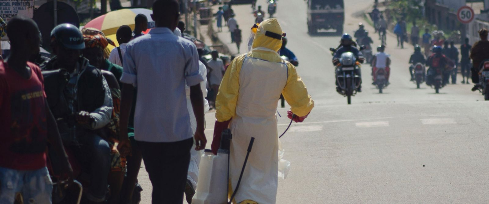 PHOTO: A health worker with disinfectant spray walks down a street outside the government hospital in Kenema, Sierra Leone on July 10, 2014.