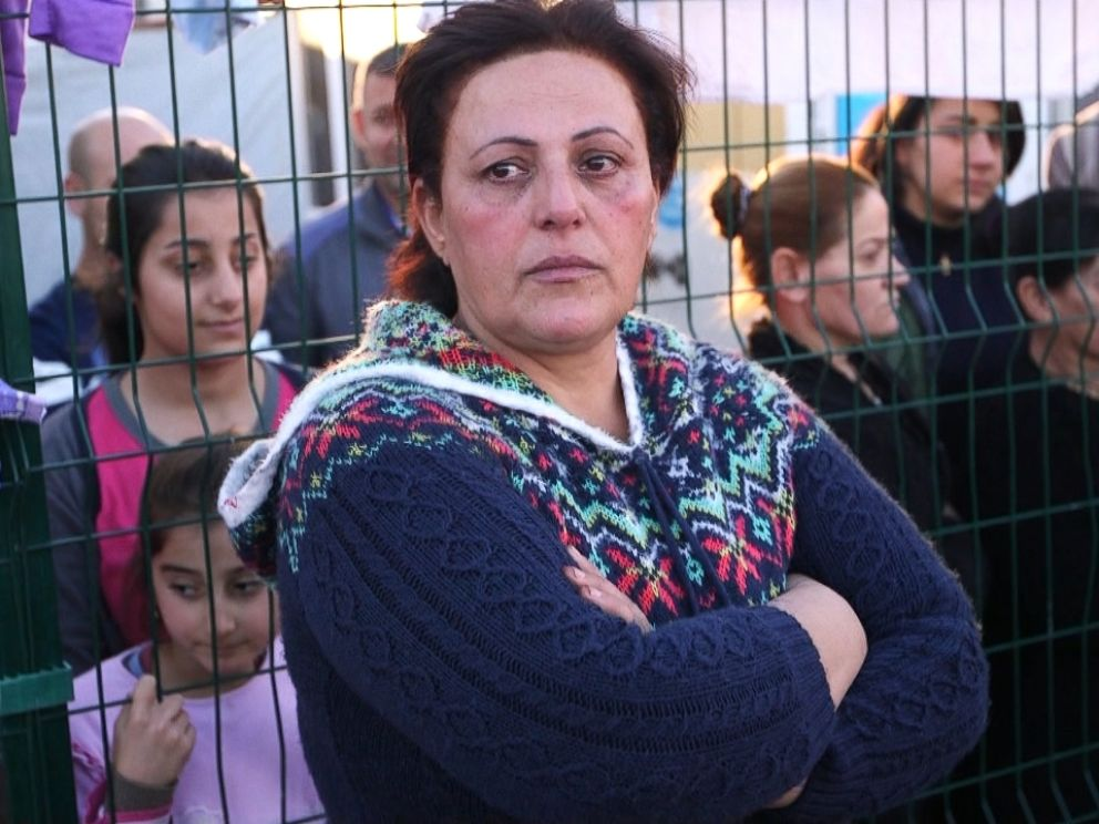Majida Habeeb Gorgees, the cook for the refugee center in Erbil, Iraq, stands by a fence.