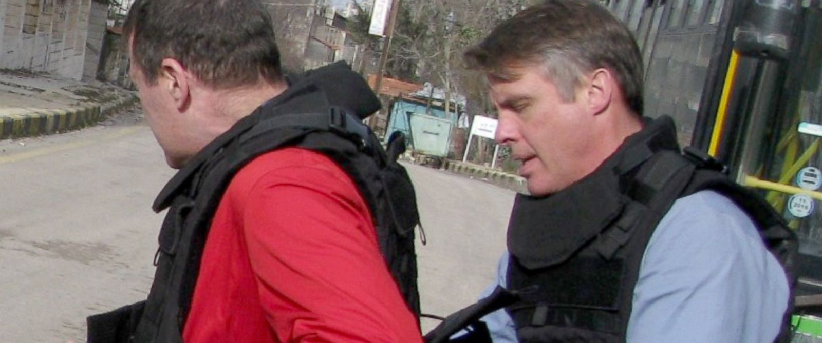 PHOTO: From the outskirts of a village, Terry Moran helps cameraman Max Karmen with his vest.