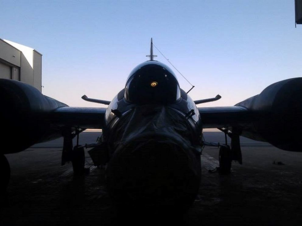 PHOTO: A WB-57 shown in shadow in a hanger in Afghanistan, its nose sensor package covered to protect from dust.