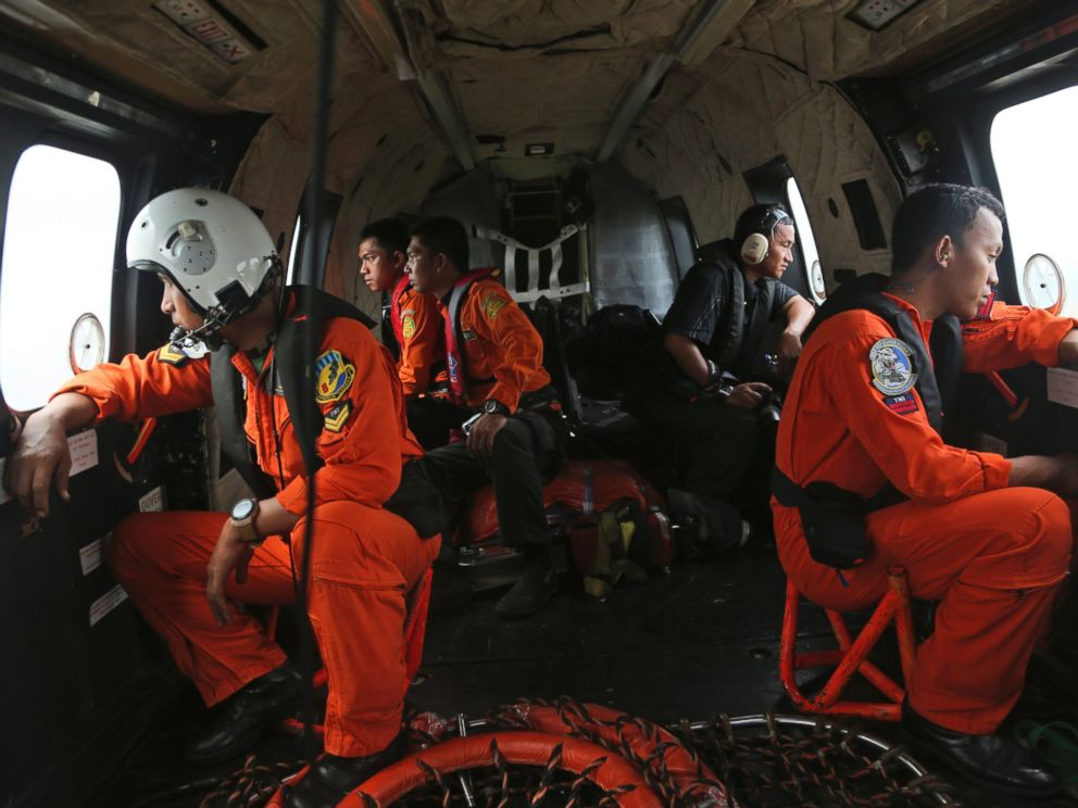 PHOTO: Crewmembers of Indonesian Air Force NAS 332 Super Puma helicopter look out of the windows during a search operation for the victims and wreckage of AirAsia Flight QZ 8501 over the Java Sea, Indonesia, Jan. 5, 2015.