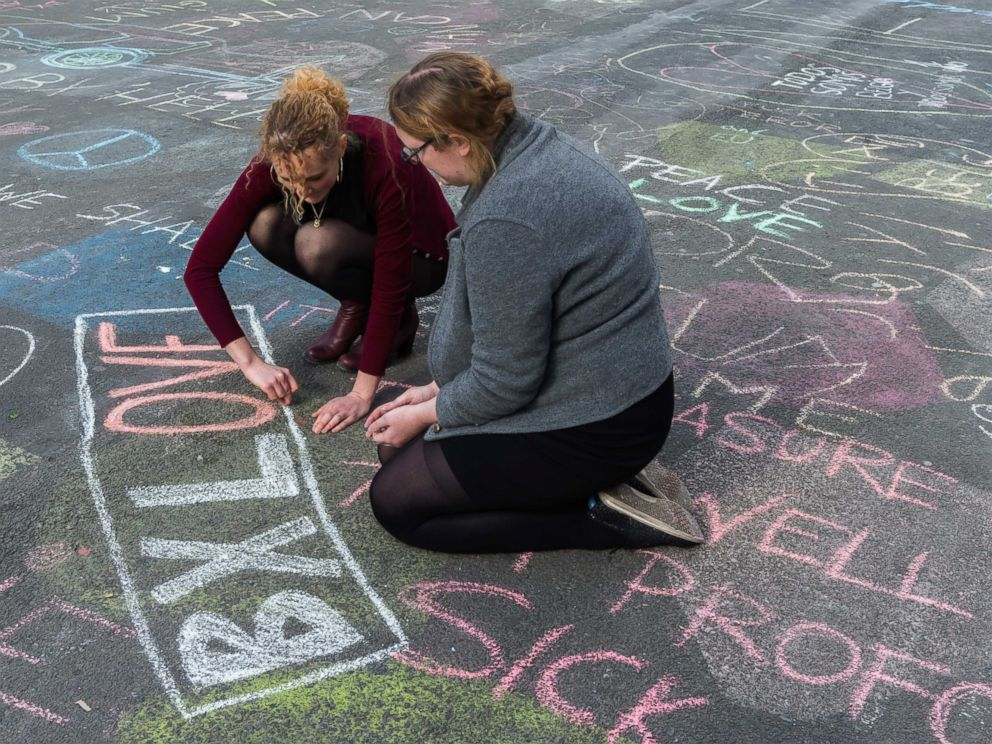 PHOTO: Two people write solidarity messages in chalk outside the stock exchange in Brussels, March 22, 2016.