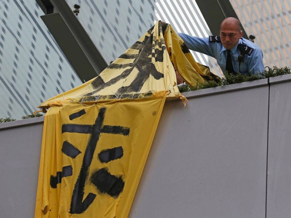 PHOTO: A police officer removes a banner on the bridge at the occupied area outside government headquarters in Hong Kong, Dec. 11, 2014.