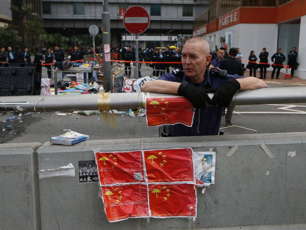 PHOTO: A police commander leans against a concrete wall with the defaced Chinese national flags placed on at the occupied area outside government headquarters in Hong Kong, Dec. 11, 2014.