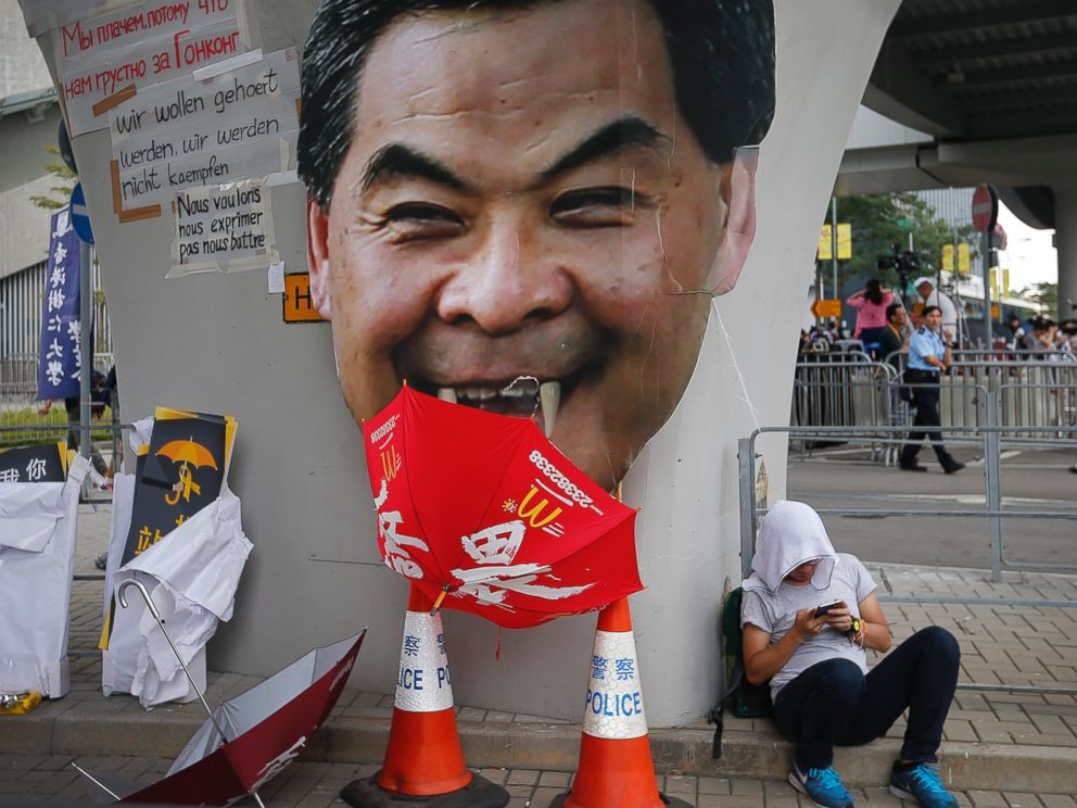 PHOTO: A student protester rests next to a defaced cut-out of Hong Kongs Chief Executive Leung Chun-ying at one of their protest sites around the government headquarters, Sept. 30, 2014, in Hong Kong.