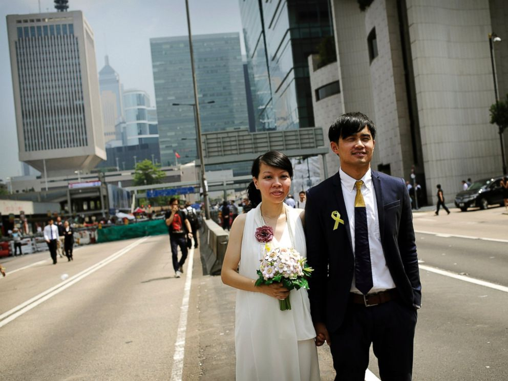 PHOTO: Newly married couple Vivian Lo and Ka Sing Fung, both 30 years old from Hong Kong, pose for their personal photographer, in front of the protest site of pro-democracy activists, Sept. 30, 2014, in Hong Kong.