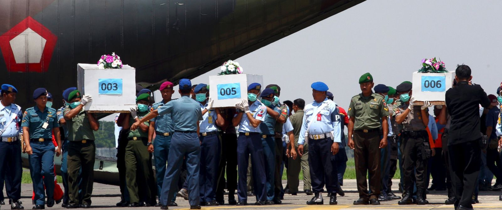 Indonesian soldiers carry coffins containing victims of AirAsia Flight 8501 upon arrival at Indonesian Military Air Force base in Surabaya, Indonesia, Thursday, Jan. 1, 2015.