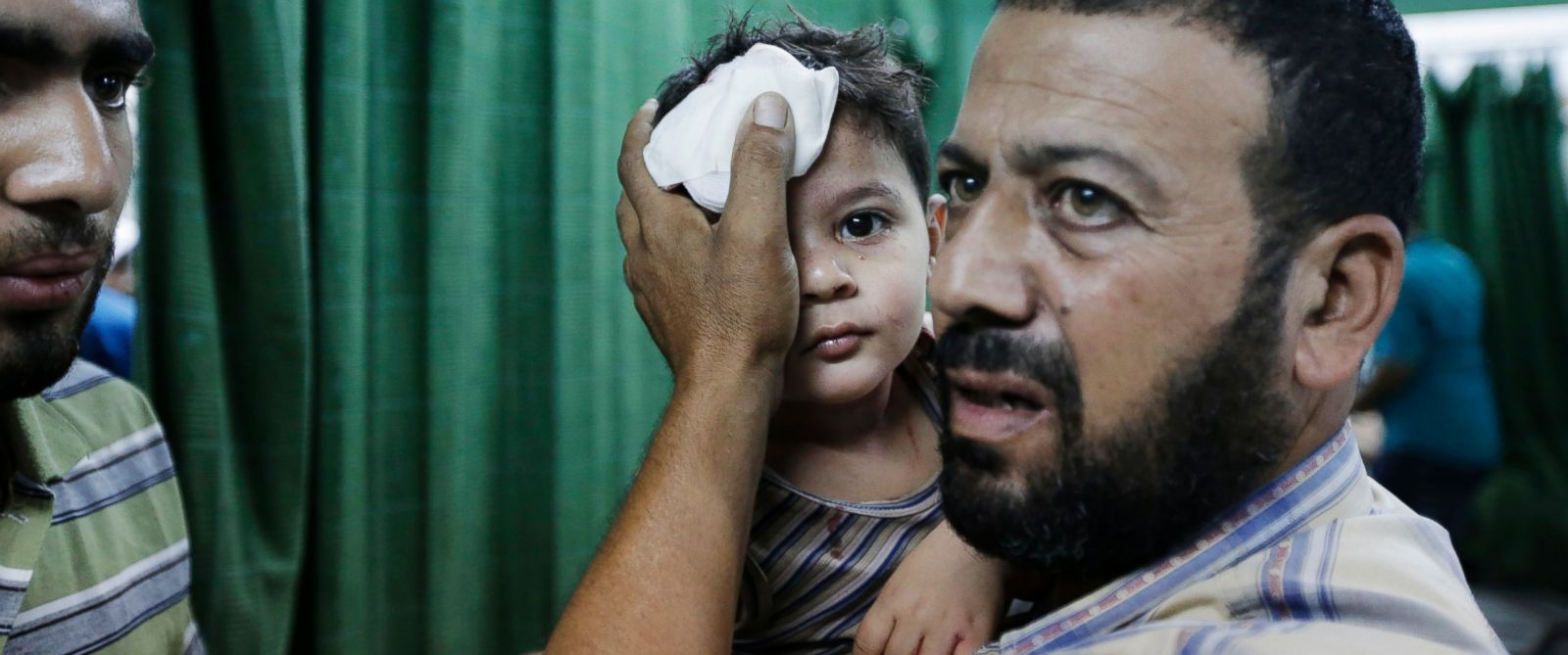 PHOTO: A Palestinian carries a boy, wounded in an Israeli strike at a house in Beit Lahiya, northern Gaza Strip, into the emergency room of the Kamal Adwan Hospital, in Beit Lahiya, Sunday, Aug. 3, 2014.