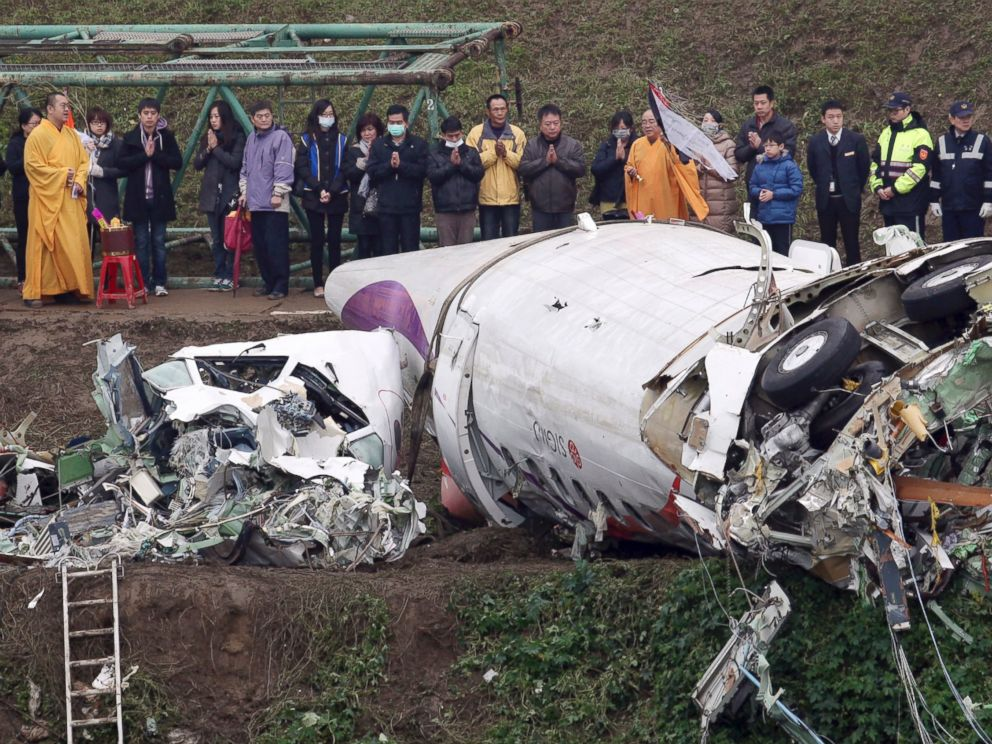 PHOTO: Relatives of the victims in a commercial plane crash pray over the wreckage along the river bank in Taipei, Taiwan, Feb. 5, 2015.