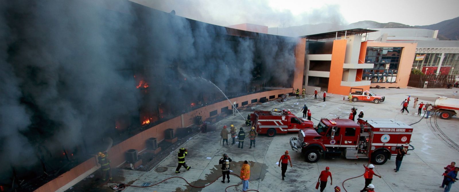 PHOTO: Firefighters try to extinguish the flames after the state capital building was set on fire by protesting college students in Chilpancingo, Mexico, Oct. 13, 2014.