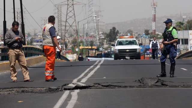 PHOTO: Emergency workers inspect a portion of a bridge that buckled after an earthquake was felt in Mexico City, Tuesday March 20, 2012.