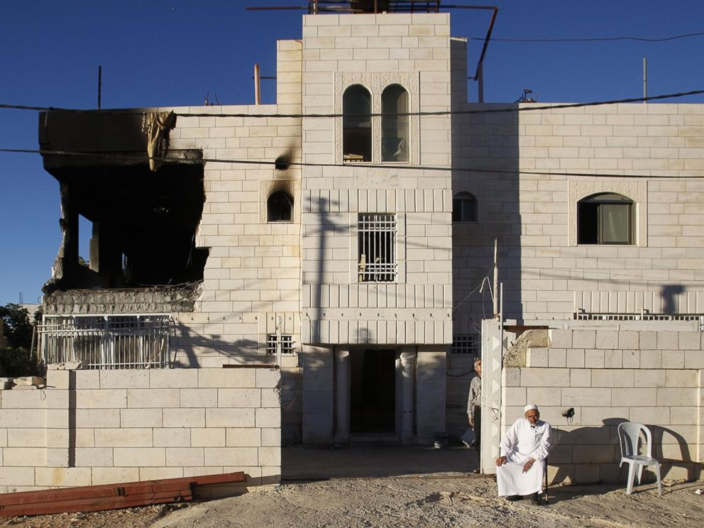PHOTO: A Palestinian sits outside a home damaged by the Israeli army in the West Bank city of Hebron, July 1, 2014.