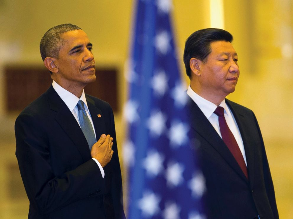 U.S. President Barack Obama places his hand on his chest as the U.S. national anthem is played at a welcome ceremony with Chinese President Xi Jinping inside the Great Hall of the People in Beijing, Nov. 12, 2014.