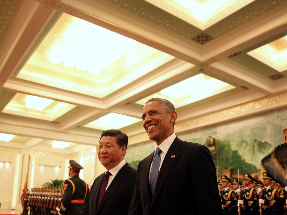 U.S. President Barack Obama, right, smiles after a group of children waved flags and flowers to cheer him during a welcome ceremony with Chinese President Xi Jinping at the Great Hall of the People in Beijing, Nov. 12, 2014.