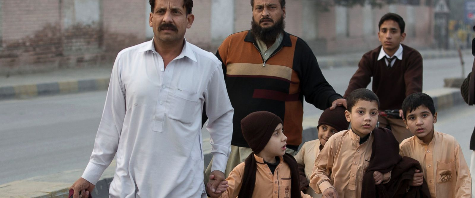 PHOTO: Pakistani parents escort their children outside a school attacked by the Taliban in Peshawar, Pakistan, Dec. 16, 2014.