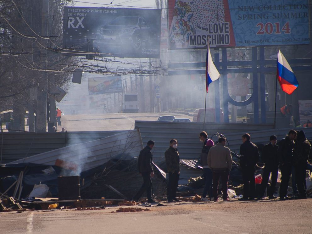 PHOTO: Pro-Russian activists gather behind a barricade with Russian flags in front an entrance of the Ukrainian regional office of the Security Service in Luhansk, 20 mile west of the Russian border, in Ukraine, April 8, 2014.