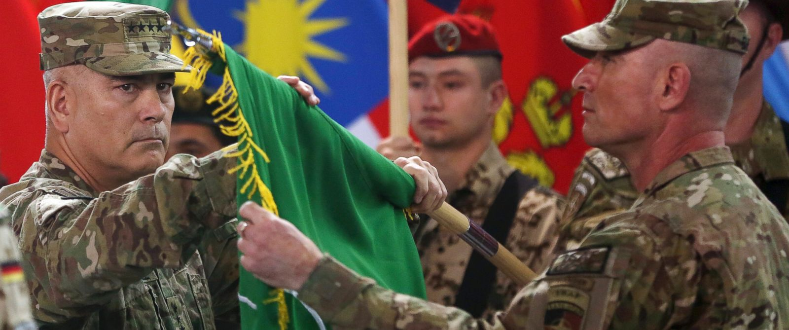 """PHOTO: Commander of the International Security Assistance Force (ISAF), Gen. John Campbell, left, and Command Sgt. Maj. Delbert Byers open the """"Resolute Support"""" flag during a ceremony at the ISAF headquarters in Kabul, Afghanistan, Dec. 28, 2014."""