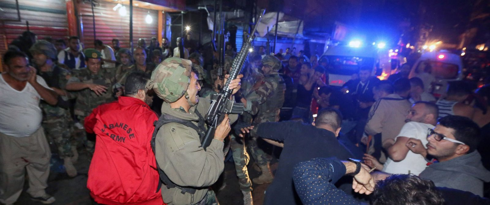 PHOTO: A Lebanese soldier opens fire into the air to disperse people who gathered around a man (on the ground) whom they claimed was a suspected attacker in Burj al-Barajneh, southern Beirut, Lebanon, Nov. 12, 2015.