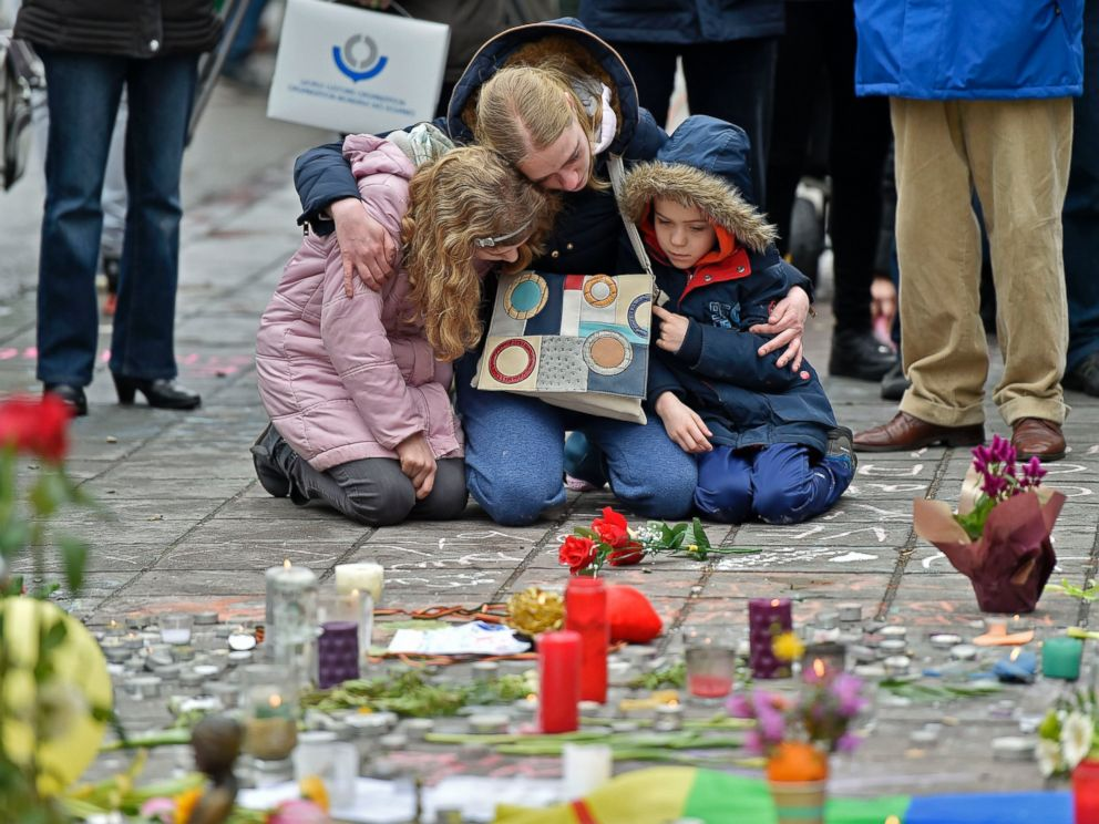 PHOTO: A woman and children sit and mourn for the victims of the bombings at the Place de la Bourse in the center of Brussels, March 23, 2016.