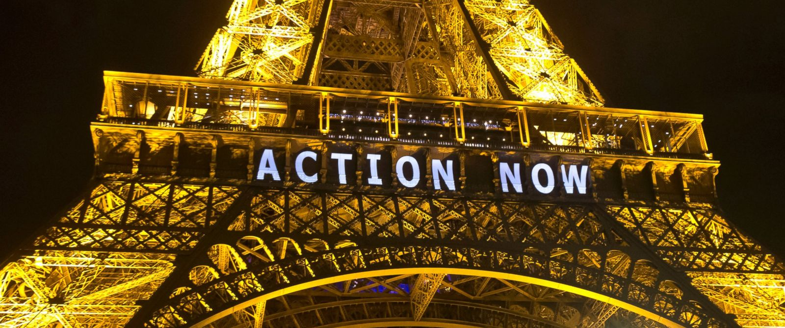 """PHOTO: The Eiffel Tower lights up with the slogan """"Action Now"""" referring to the COP21, United Nations Climate Change Conference in Paris, Dec. 6, 2015."""