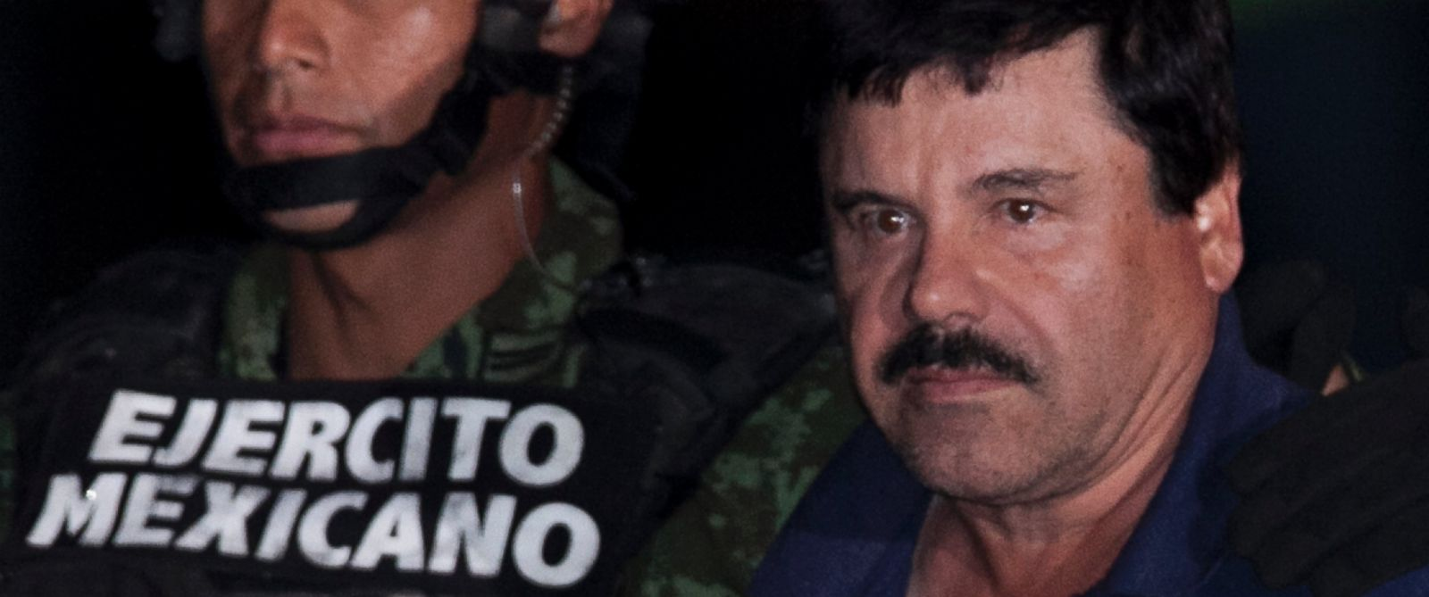 """PHOTO: Mexican drug lord Joaquin """"El Chapo"""" Guzman, right, is escorted by soldiers and marines to a waiting helicopter, at a federal hangar in Mexico City, Jan. 8, 2016."""