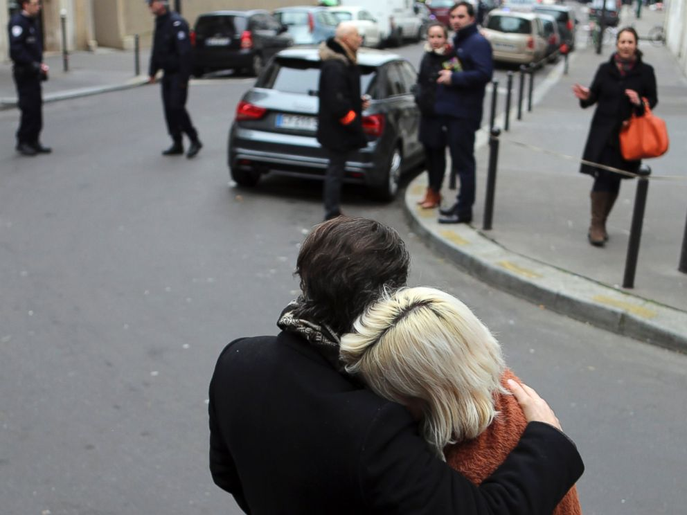 PHOTO: People stand outside the French satirical newspaper Charlie Hebdos office after a shooting, in Paris, Jan. 7, 2015.