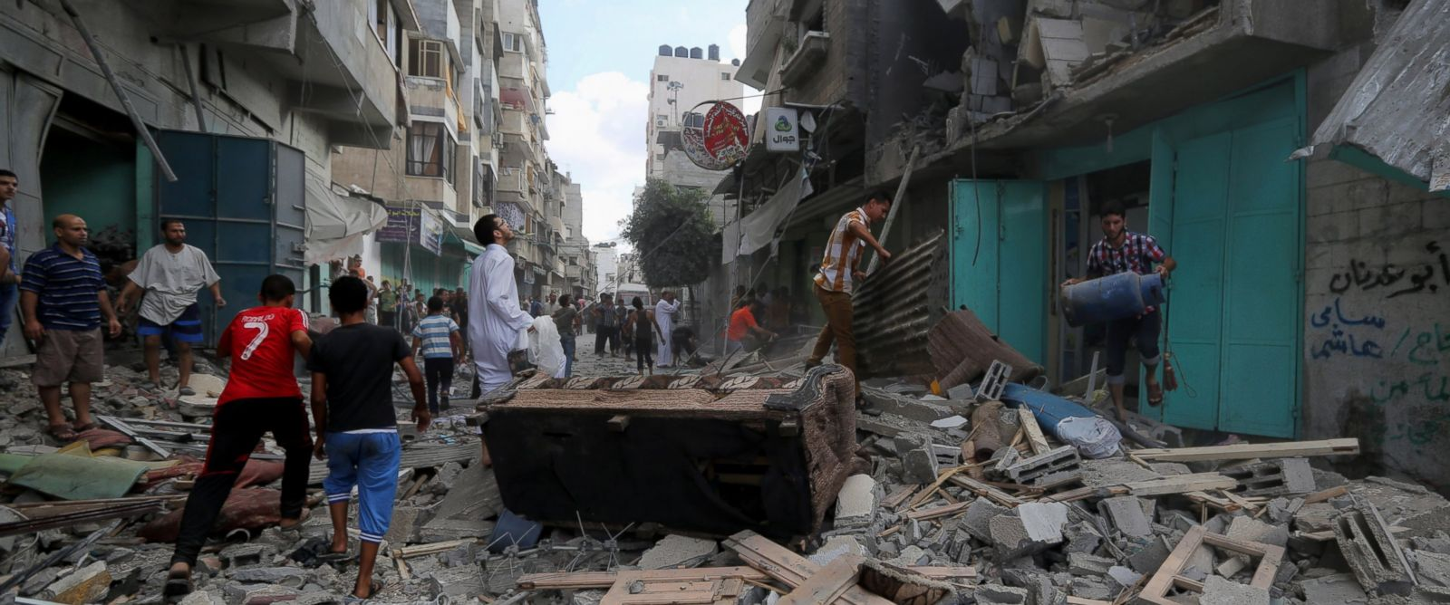 PHOTO: Palestinians inspect the rubble of a building as they pick up their usable belongings