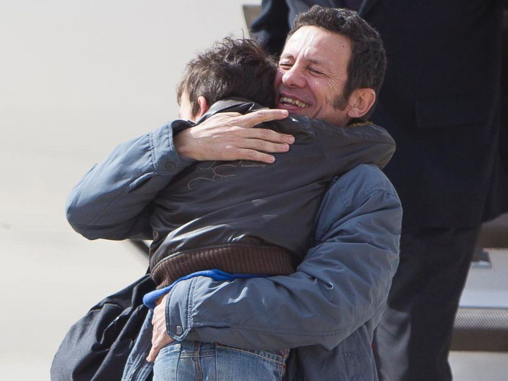 PHOTO: Spanish reporter Javier Espinosa hugs as his son Yerai upon his arrival at the military airport of Torrejon in Madrid, Sunday, March 30, 2014.