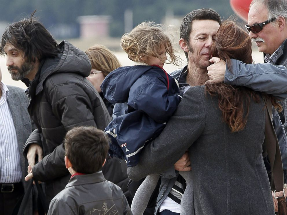 PHOTO: Spanish reporter Javier Espinosa, second right, holds his daughter Nur as he is greeted by his wife Monica Garcia upon his arrival at the military airport of Torrejon in Madrid, Sunday, March 30, 2014.