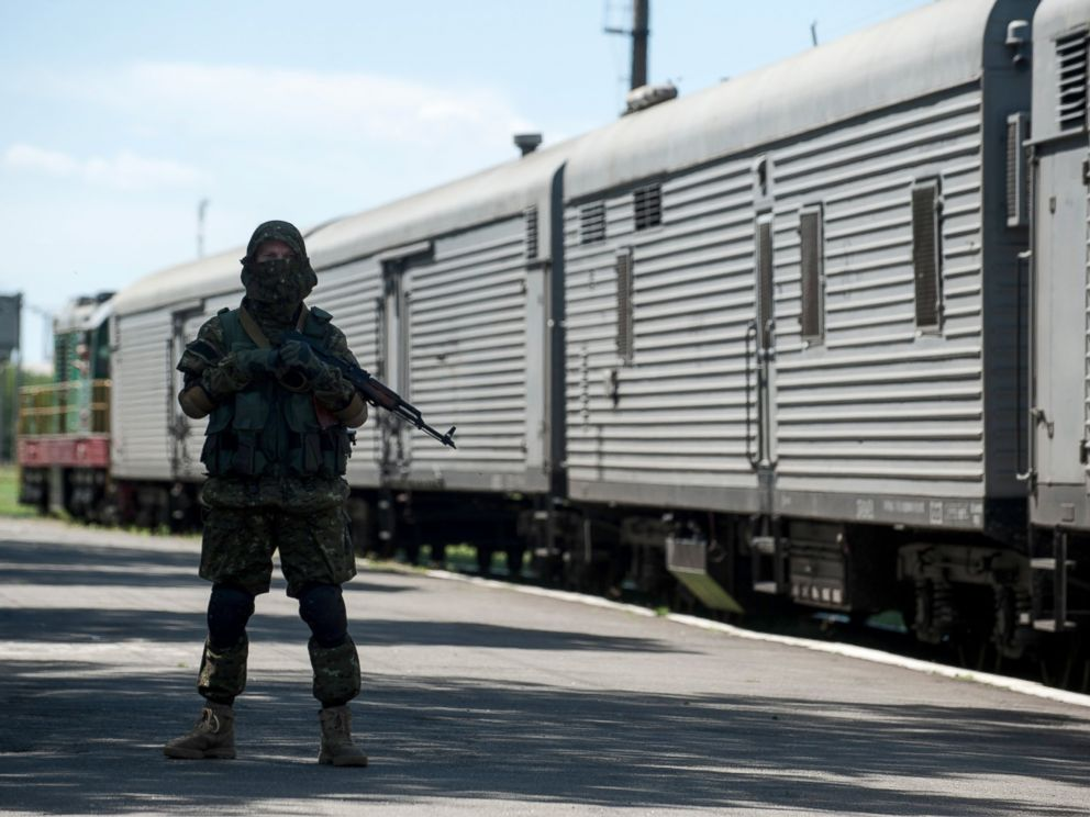 PHOTO: A pro-Russian armed fighter stands in guard on the platform as a refrigerated train loaded with bodies of the passengers departs the station in Torez, Ukraine, near the crash site of Malaysia Airlines Flight 17, July 21, 2014.
