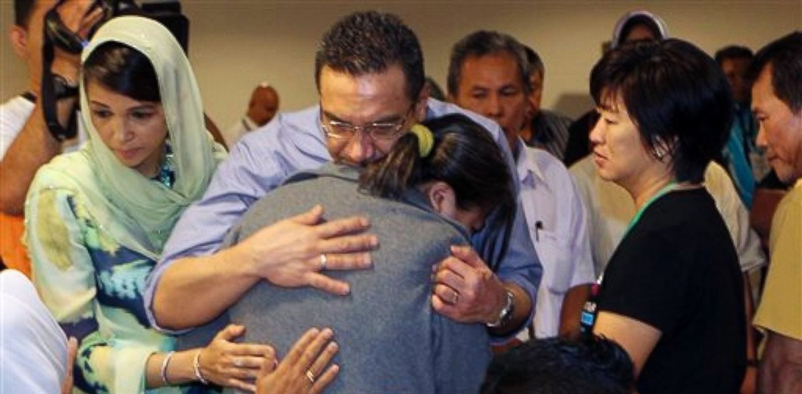 PHOTO: Malaysias acting Transport Minister Hishammuddin Hussein, center, comforts a relative of passengers on board the missing Malaysia Airlines flight MH370 at a hotel in Putrajaya, Malaysia, Saturday March 29, 2014.