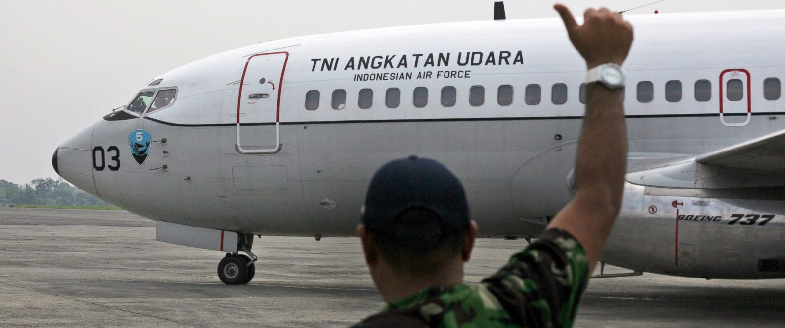 "PHOTO: A ground crew gives an OK sign to the pilots of an Indonesian Air Force Boeing 737 ""Surveiller"" as they prepare to take off for a search operation for the missing Malaysia Airlines jetliner MH370, in Indonesia, Saturday, March 15, 2014."