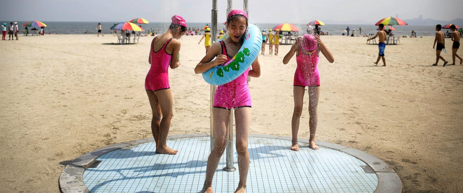 PHOTO: North Korean girls in similar bathing suits stand under a shower at the Songdowon International Childrens Camp, July 29, 2014, in Wonsan, North Korea.