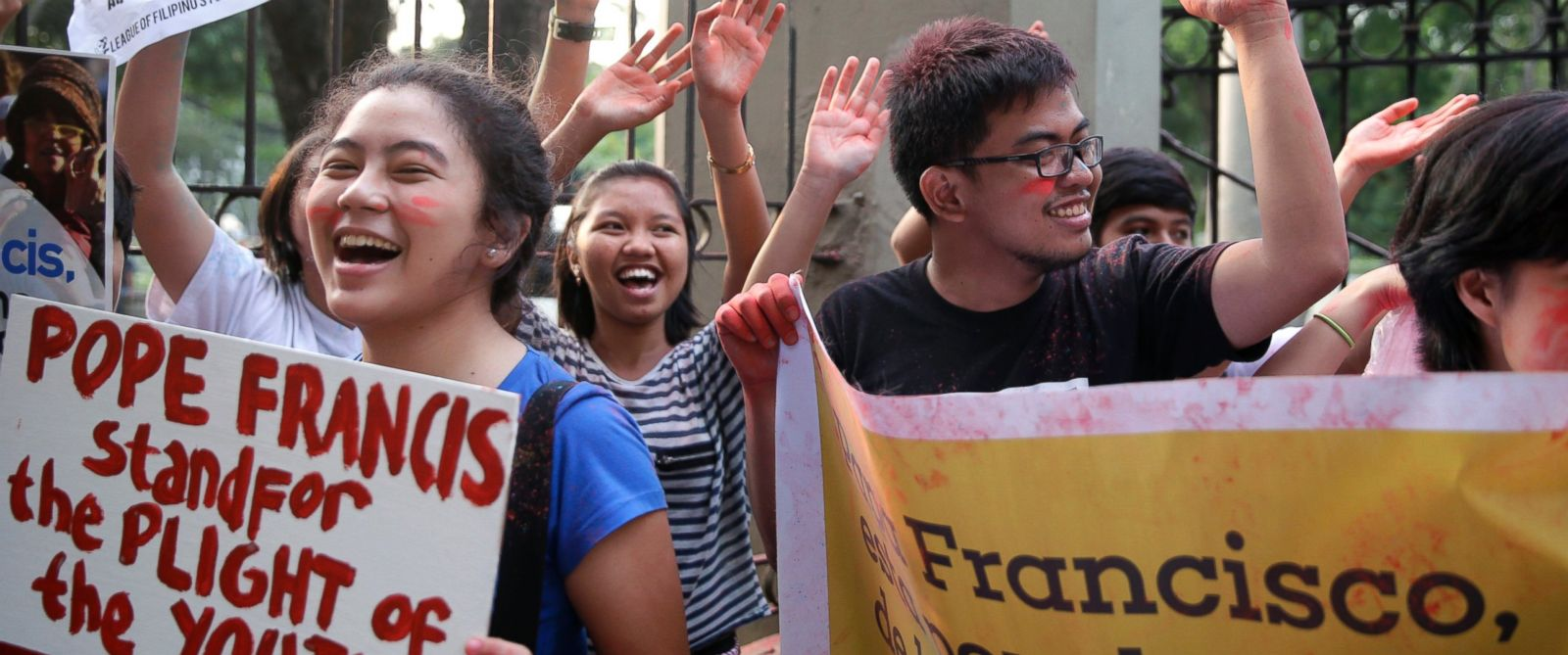"""PHOTO: Youth and students shout """"Welcome Pope Francis"""" after throwing colored powder in the air at the start of the countdown to welcome the Pontiff, Jan. 14, 2015 in Manila, Philippines."""